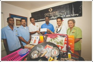 Anoop Naidu receives the donation from the Outrigger Staff